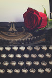 one red rose on vintage typewriter with blank page, retro toned