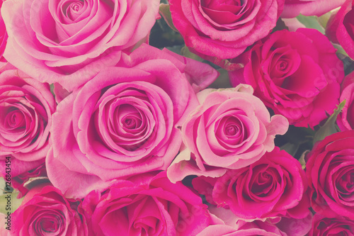 Poster round bouquet of pink and magenta roses close up background, retro toned