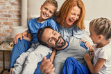 Happy family lying down on bed at home - 126844651