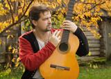 Man playing guitar in autumn garden