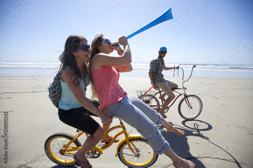 Poster Two women and one man riding bikes, having fun on the beach in San Diego, California