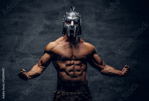 Muscular man in a gladiator silver helmet. Poster