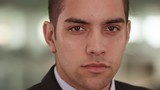 Close up portrait of Confident Latino businessman in office looking at camera. Serious young Hispanic business worker