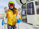 Girl teenager skier go out with ski on arms from the cable car i