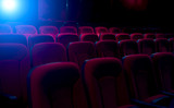 Dark film theater with projection light and empty seats - 126919268