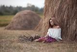 деревенский вечер в испании 19 века , красивая девушка сидит около стога сена и грустит о своем парне .