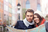 Pretty couple sightseeing with map