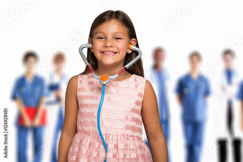 Fotografiet Child using a toy stethoscope in front of a group of doctors