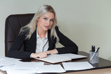 beautiful businesswoman in suit sitting at the table with documents