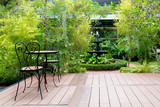 Black chair in wood patio at green garden with fountain in house - 126935490