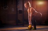 Fototapety Attractive blonde girl exercising with kettlebell