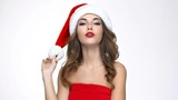Attractive young woman in santa claus costume standing and sending kiss to camera