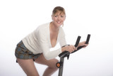 Middle aged woman working out on an exercise bike - 2016