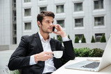 Businessman talking on mobile phone and drinking coffee in cafe