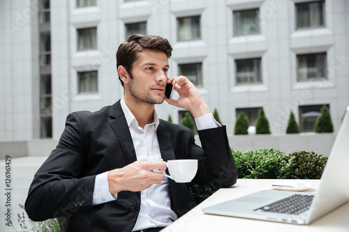 Businessman talking on mobile phone and drinking coffee in cafe Poster