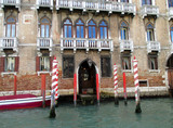 Red and white Gondola mooring poles in front of a beautiful building on the Grand Canal of Venice, Italy