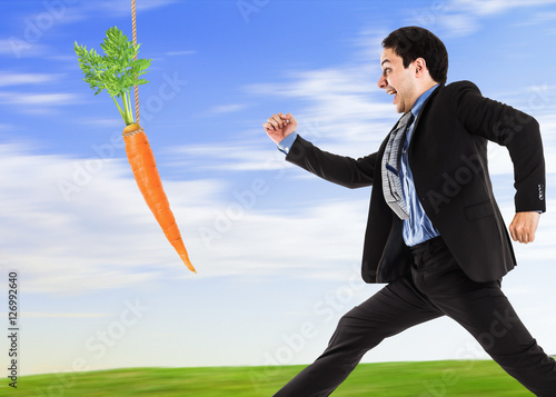 Businessman trying to take a carrot Poster
