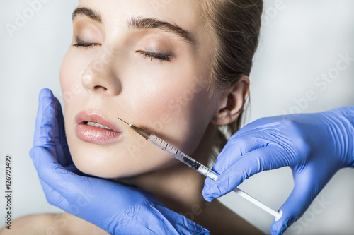 Doctor aesthetician makes lips correction and augmentation to female patient © pavelgulea