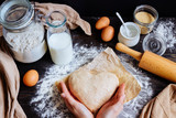 female hands holding dough in heart shape top view. Baking ingredients on the dark wooden table - 126993611