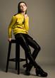 Beautiful fashion model with yellow jumper sitting
