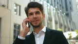 Handsome smiling businessman wearing classical style of clothes, talking on phone.