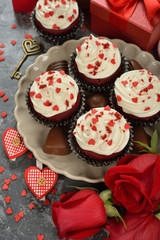 Cupcakes, chocolate and rose on a gray background