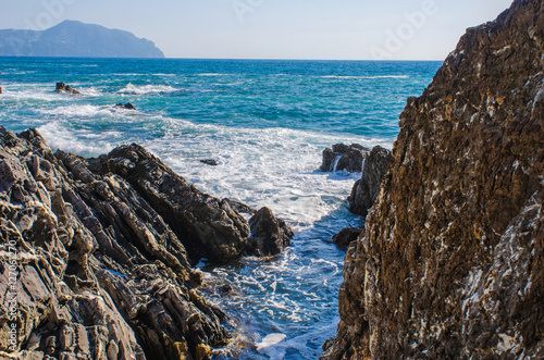 Foto op Canvas Liguria small water torrent between the cliffs at the rocky shore of the Mediterranean sea in Genoa Nervi, Italy, with a view to the horizon and the mountains in the distance