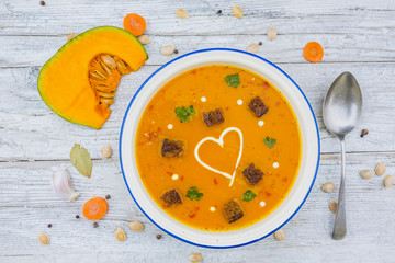 Creamy pumpkin soup with herbs and cream in the shape of hearts. Vegetarian food.
