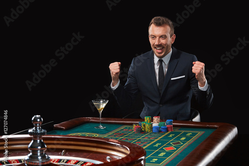 man in suit playing roulette. addiction to gambling. плакат