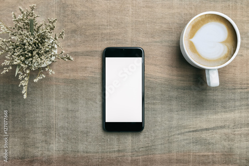 Mobile smart phone with coffee latte cup and flowers on wood tab