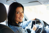 Happy woman in the car with mobile phone