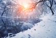 Winter forest on the river at sunset. Colorful landscape with snowy trees, frozen river with reflection in water. Seasonal. Winter trees, lake, sun and blue sky. Beautiful snowy winter in countryside