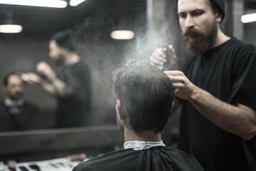 Barber is using spray bottle