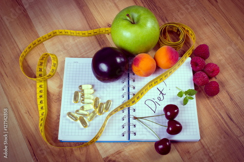 Vintage photo, Fruits, tablets supplements and centimeter with notebook, slimming and healthy food