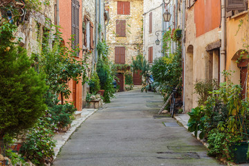 Street with flowers in the old town in France.