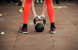 Woman athlete holding a kettlebell close up