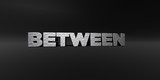 BETWEEN - hammered metal finish text on black studio - 3D rendered royalty free stock photo. This image can be used for an online website banner ad or a print postcard.