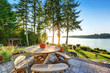 Back yard of waterfront house with rustic wooden table set