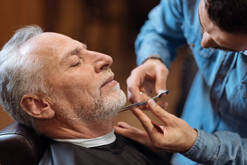 Barber cutting beard of senior client with scissors