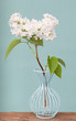 A bunch of white lilac flowers in a wire base on a wooden surface