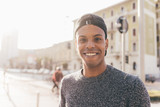 Young handsome american african man outdoor in city back light, looking at camera smiling - rebel, happiness, thoughtless concept