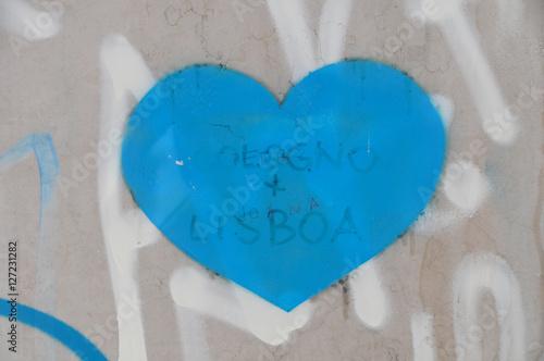 Poster blaues Herz auf Wand mit Sprayerei in Lissabon