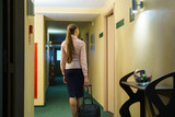 Young woman looking for her room in hotel