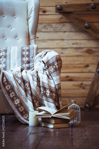 Poster Stack of books with warm plaid on chair