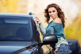Young fashion woman with long curly hairs standing next to her car