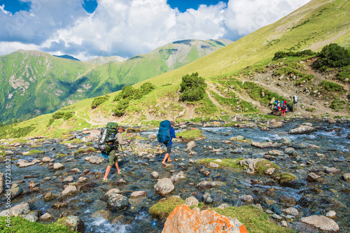 A group of tourists goes to ford a mountain river, Kyrgyzstan. Poster