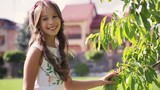 Little brunette girl in a white dress is walking cross the fruit garden, touches the leaves of the tree, turns to camera and smiles. Moments of happiness. Children portrait. Happy childhood.