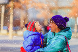 mother and son enjoy first snow, family winter in the city