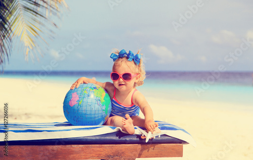 Fotografiet family travel - little girl with globe and toy plane on beach