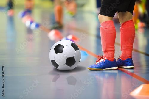 Children training soccer futsal indoor gym. Young boy with soccer ball training indoor football. Little player in light red sports socks